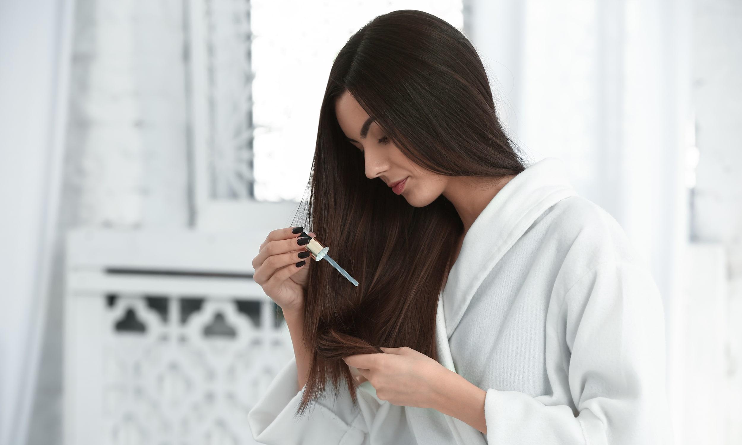 девушка использует масляную сыворотку для волос против выпадения волос