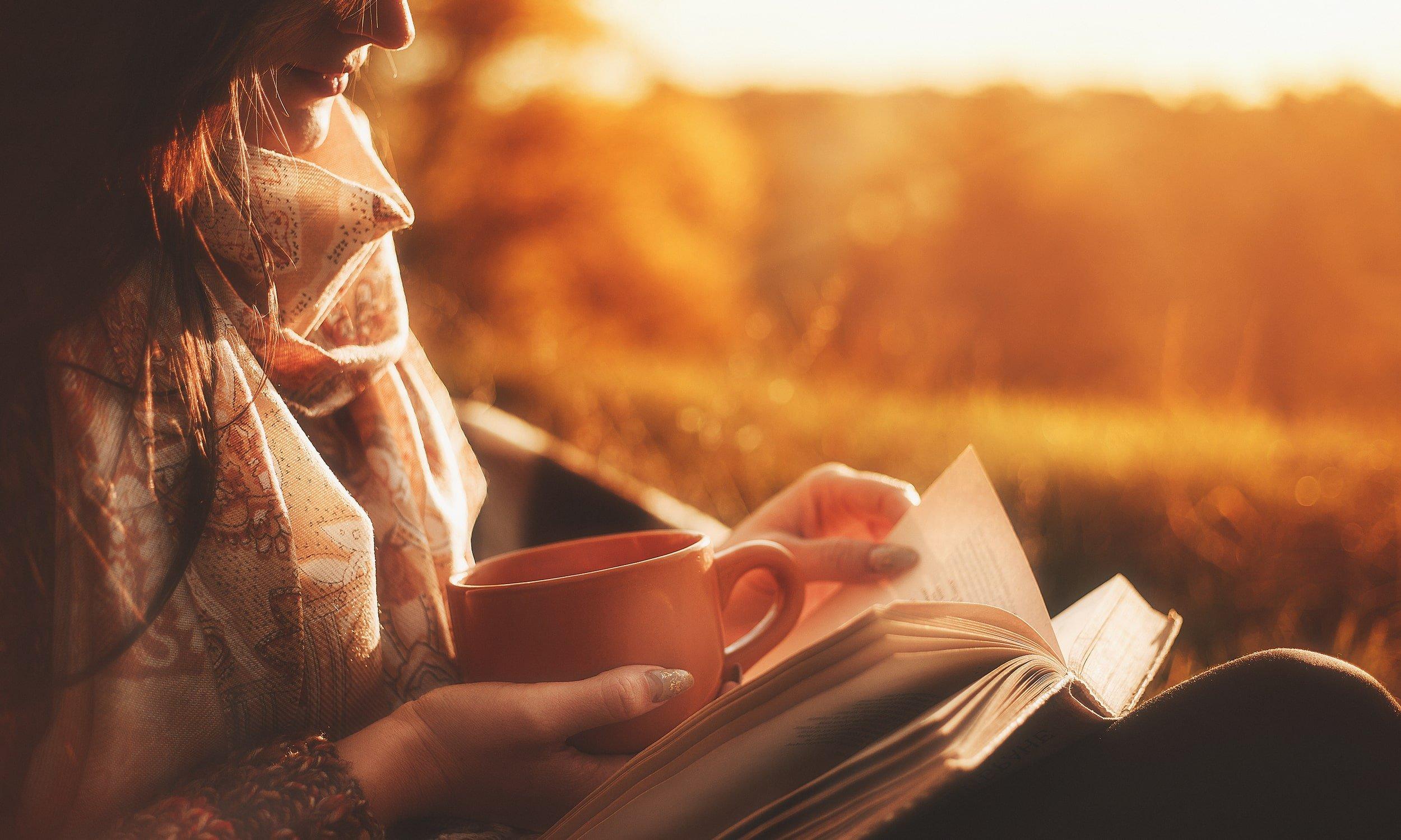 sieviete lasa gramatu un dzer kafiju